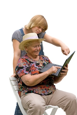 Senior woman and her granddaughter with a computer on white background photo