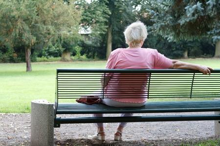 Senior femme est assise seule dans un parc