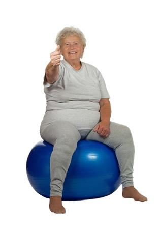 1 senior: Mujer senior feliz da Aceptar en un fitball, sobre fondo blanco