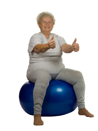 Happy senior woman gives OK on a fitball, on white background Stock Photo - 10324669