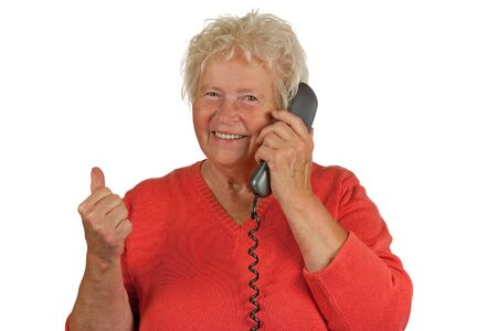 all right: Senior woman makes OK gesture with a telephone