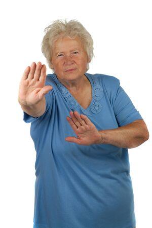 stop gesture: Senior woman is making stop gesture , on white background
