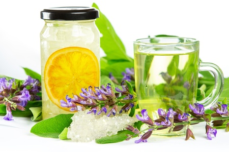 naturopathy: Glass of sweet herbal tea with flowering salvia and sage, sugar crystals and sliced orange, a medicinal remedy used in Auyurveda naturopathy Stock Photo