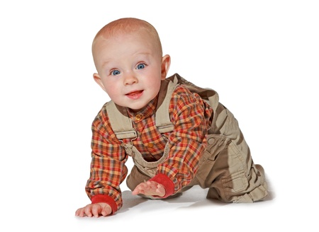 explores: Cute alert baby crawling towards the camera dressed in a checked shirt and dungarees as it explores the surroundings Stock Photo