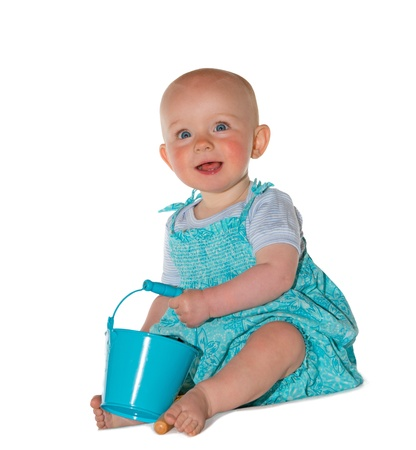 trusting: Adorable baby with an alert trusting expression dressed in a pretty turquoise outfit sitting on the floor playing with a bucket