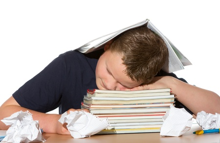 Tired out by studying for exams a young teenage boy has fallen asleep with his head resting on his textbooks and crumpled paper lying scattered around him Stock Photo - 14129270