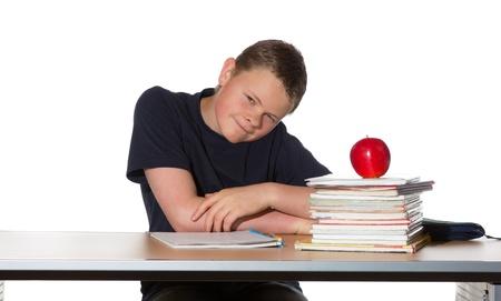 quizzical: Adolescente sentado en su escritorio mirando a la c�mara con una expresi�n burlona con la pila de libros y una saludable manzana madura roja