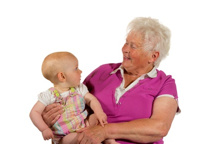 Trusting young baby cradled in its grandmothers arms looking up at her smiling face photo