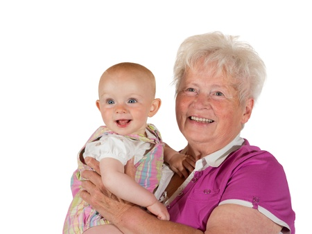 The joy of being a grandmother, a beaming, joful young baby and doting grandmother smile happily for the camera while posing for a studio portrait photo
