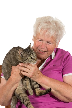Happy grey-haired retired lady smiling as she holds her alert cat in both hands isolated on white photo
