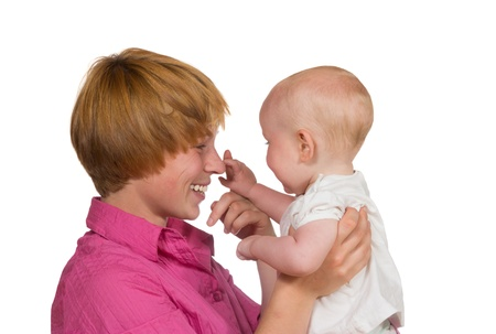 10 month: Cute young baby looking away from the camera gently touching the nose of its happy smiling mother Stock Photo