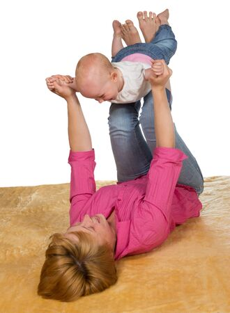 Young mother lying on her back on the floor playing with her baby which is balanced on her raised legs with its arms outstretched photo