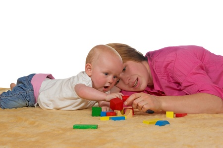 10 month: Mum and her small baby lying close together on the floor playing with building blocks as she teaches it coordination and shapes Stock Photo