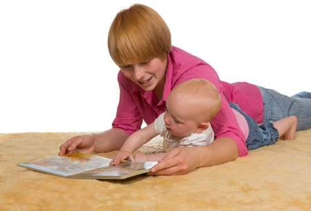 Mother lying on the floor with her arm protectively around her cute young baby looking at a book together photo
