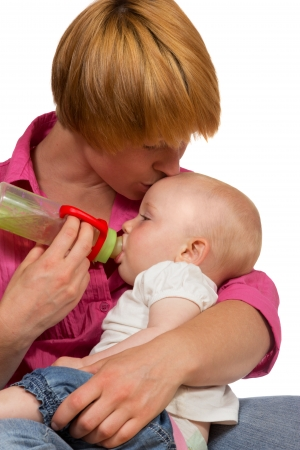 Young Mum bottlefeeding her adorable small baby cradled in her arms as she kisses it lovingly on the forehead photo