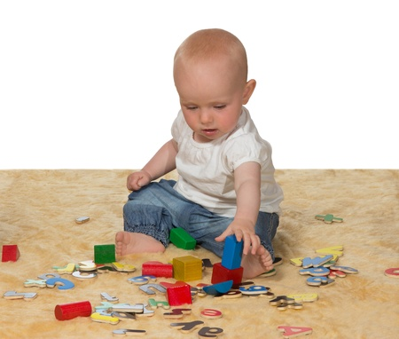 Adorable young baby, 10 months old, sitting contentedly on the floor playing with an assortment of educational toys photo