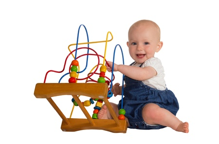 stimulation: Happy cute baby playing on the floor with a wooden educational toy with looped wires for teaching coordination and colours isolated on white Stock Photo