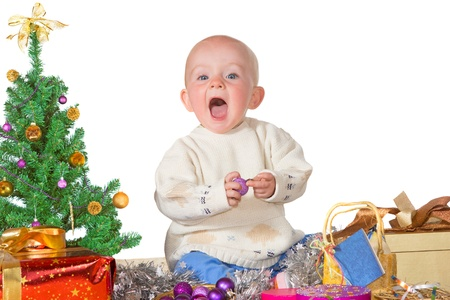Cute little baby laughing in excitement surrounded by gifts, decorations and a tree enjoying Christmas photo