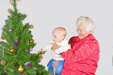 A happy smiling grandmother holds a cute young baby in her arms as they inspect a decorated Christmas tree photo