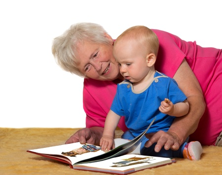 stimulate: A doting Grandmother lies on the floor with her cute baby grandchild reading a picture book to teach and stimulate the youngsters mind