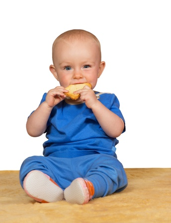 contentment: Adorable small baby sitting on the carpet eating a bun with a look of contentment against a white background Stock Photo