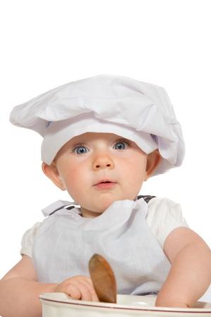 Adorable baby in chef-koks hoed spelen met een houten lepel en kom met een grote ogen expressie van ontzag en verwondering op wit wordt geïsoleerd Stockfoto