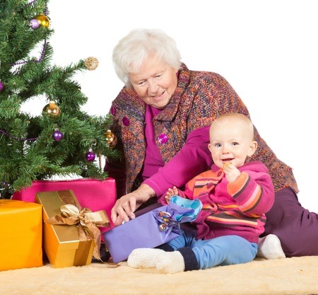 babysitting: Grandmother babysitting young baby sitting together on the floor alongside a decorated Christmas tree and giftwrapped presents