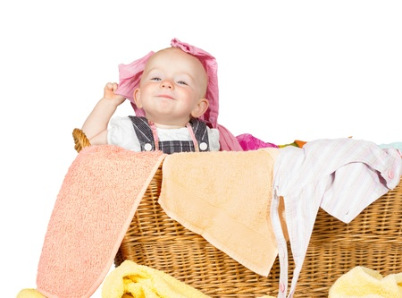 Impish little baby with a cute little self-satisfied expression sitting in amongst the washing in a wicker laundry basket photo