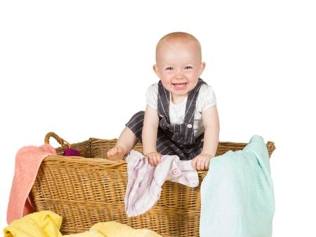 clamber: Laughing baby con un sorriso raggiante giocare in un grande cesto di vimini lavanderia e comincia ad arrampicarsi fuori isolato su bianco