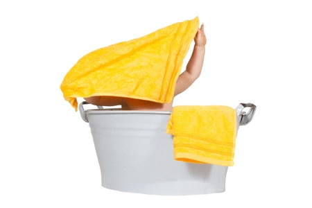 aloft: Mischievous baby sitting in a zinc bath tub playing with a yellow towel which it is holding aloft hiding its face