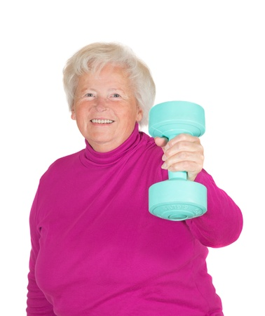 flexed: Cheerful senior woman lifting weights holding up a dumbbell in her flexed arm in a health and fitness concept Stock Photo