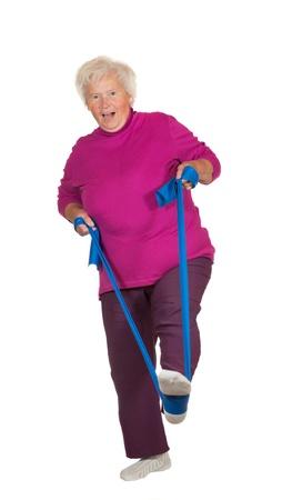 apalancamiento: Retried mujer con sobrepeso senior ejercer con una correa de influencia para mejorar el equilibrio y la coordinaci�n muscular aislado en blanco