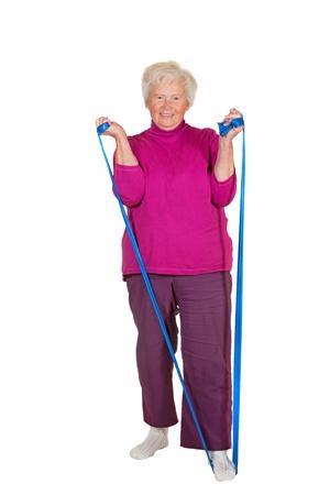 apalancamiento: Un alegre ejercicios ancianos jubilada con una correa colocada bajo su pie como palanca para strengthnen brazo y los m�sculos del est�mago