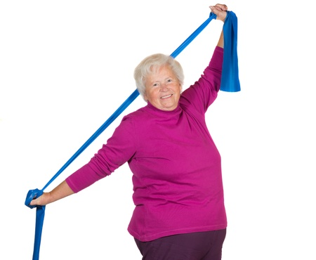 Happy overweight senior lady exercising stretching her arms above her head using a strap to improve her flexibility and strengthen her neck and shoulder muscles