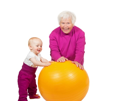 Laughing grandmother pausing in her exercises as her inquisitive little baby grandchild comes over to investigate the pilatses ball