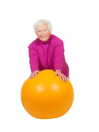 Cheerful retired lady leaning on a bright yellow pilates ball as she uses muscle control to improve her fitness and health photo