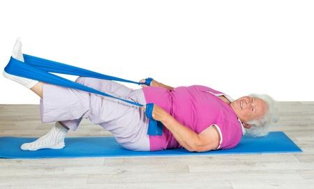 apalancamiento: Sobrepeso mujer mayor llena de entusiasmo y vitalidad ejercita en una estera de gimnasio con su pierna levantada en el aire usando una correa para aprovechar