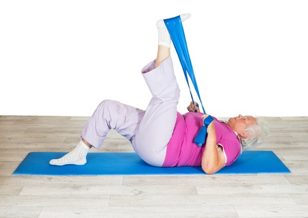 leverage: Senior woman exercising for mobility lying on a mat raising her leg in the air using a strap for leverage to improve mobility in her hip