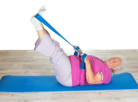 strengthen: Retired lady doing exercises lying on a gym mat raising her legs in the air to strengthen her abdominal muscles