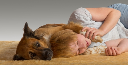 Woman lying on the floor enjoying a peaceful slumber with her head resting between the paws of her gentle protective dog photo