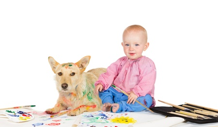 dabbling: Adorable happy little baby sitting on the floor with paintbrushes and paints alongside a dog busy painting on paper