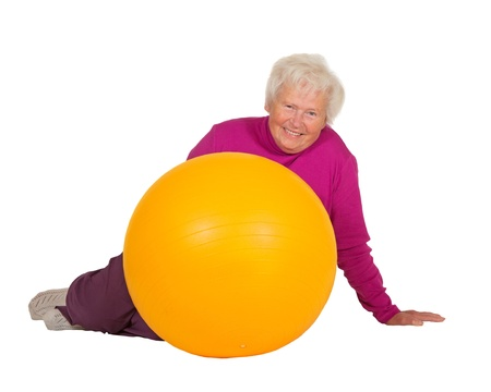 Healthy retired woman with a radiant smile full of vitality resting on the floor alongside her gym or pilates ball after a workout isolated on white photo