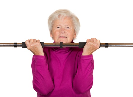 Elderly grey-haired retired woman doing a workout lifting a pole against counterweights in a health, fitness and longevity concept isolated on white photo