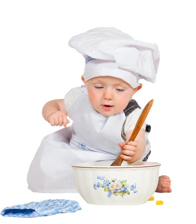 Cute little baby baking biscuits leaning forwards to inspect the ingredients in the mixing bowl seated on the floor in an apron and toque isolated on white photo