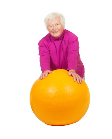 Healthy smiling retired woman full of vitality exercising with a colourful yellow pilates or gym ball isolated on white photo