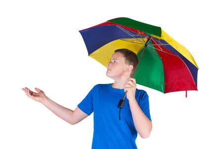 whether: Handsome young man holding a rainbow coloured umbrella over his head for protection while extending his hand to check whether it is raining isolated on white