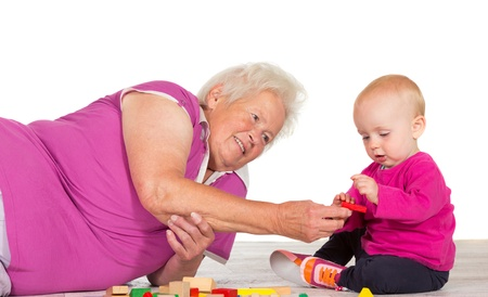 babysitting: Elderly grandmother lying on the floor babysitting her small grandchild as the two play contentedly together with toy blocks
