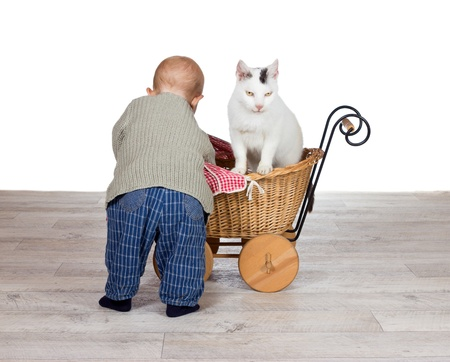 Rear view of a cute young baby bending over a toy wicker pram arranging the blanket for the family cat who is getting a ride photo