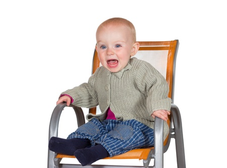 Distressed tearful baby with its mouth wide open in anguish sitting alone in a childs highchair Stock Photo - 15370027