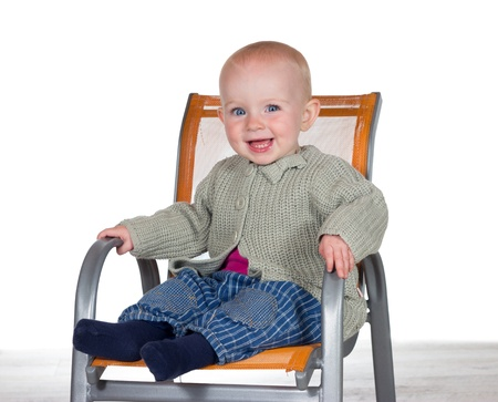 Happy smiling baby sitting alone in a stylish modern childs highchair with copyspace Stock Photo - 15370028